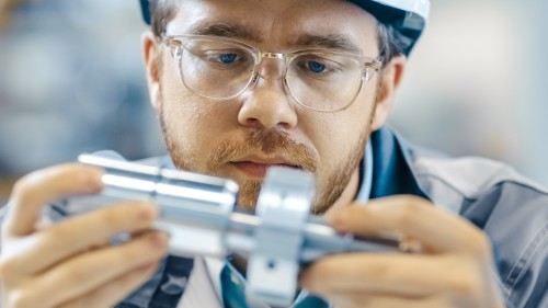 Close Up Shot Of The Industrial Engineer Wearing Classes And Hard Hat Connects Two Components He Designed. Precision In Mechanical Engineering.